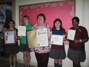 Roberta Willard and her students display honors bestowed on the St. Saviour H.S. teacher. From left: a framed profile article of Willard; a letter of thanks from Sen. Kirsten Gillibrand; a proclamation of Roberta Willard Day from Borough President Marty Markowitz; a certificate of appreciation from Gov. Andrew Cuomo; and a letter of thanks from President Barack Obama.
