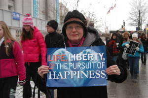 Catherine Woesthoff, a parishioner at Holy Family, Flushing, did not let the cold weather stop her as she marched in the 40th annual March for Life Jan. 25 in Washington, D.C. She's posing with the official Diocese of Brooklyn sign for the march.  (Photo by Jim Mancari)