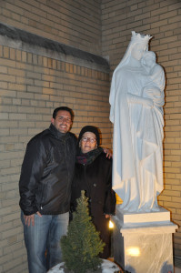 Outside St. Margaret Church, Mike Repole hugs his grandmother Assunta Guarnaccia at the new statue of Mary, Mother of God in Middle Village. (Photo by Marie Elena Giossi)