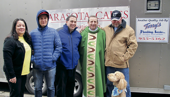 The donations from Sarasota arrived safely in Red Hook. Standing from left is, Diana Coriat, parochial director of Sandy relief; Terry Roberts' half-brother; Vincent Le Vien, director of external affairs for the DeSales Media Group; Father Claudio Antecini, pastor; Roberts, volunteer truck driver; and Lucy, the driver's service dog.