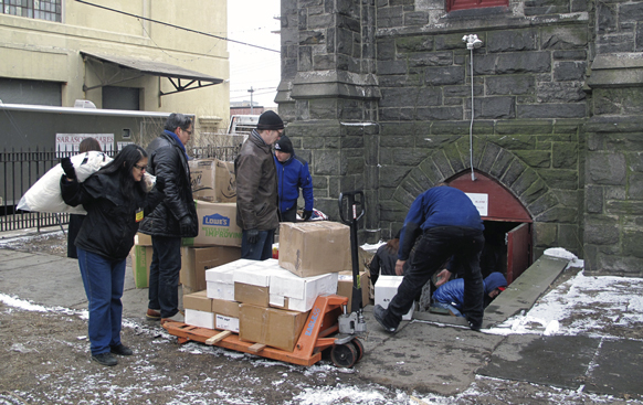 Diocesan and parish representatives do some heavy lifting to help Red Hook. They unloaded goods donated from Florida into the basement of Visitation of the Blessed Virgin Mary Church, Red Hook, where they were stored until they could be distrubuted to the people of the neighborhood.