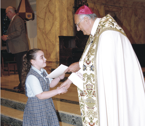 Bishop Nicholas DiMarzio presents an award certificate to one of 157 diocesan Catholic school children of Italian-American descent who received scholarships from the Tri-State Italian American Congress this school year. In the background, at left, Dr. Thomas Chadzutko, superintendent for Catholic Schools Support Services.
