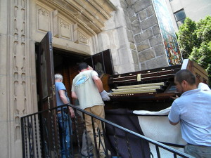 Movers carry the restored Our Lady of Refuge's pipe organ's main console up the parish stairs and into the church building. It took the entire crew to carry the largest piece into the church safely. Two trucks were unloaded the morning of June 17, and the anticipated goal for complete re-installation is mid-September, just in time for French organist Olivier Latry's rededication conert on Oct. 18. (Photo by Jim Mancari)