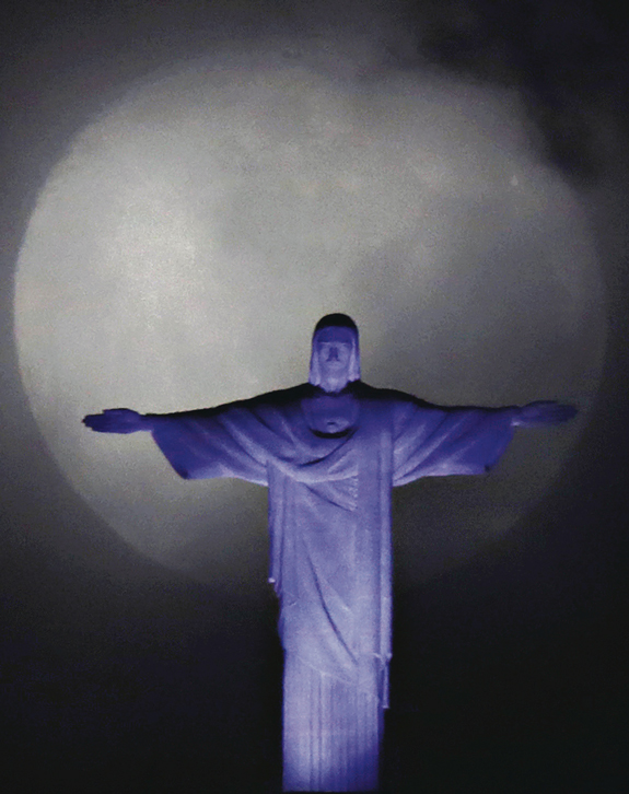 the moon is seen behind the Christ the Redeemer statue in Rio de Janeiro.
