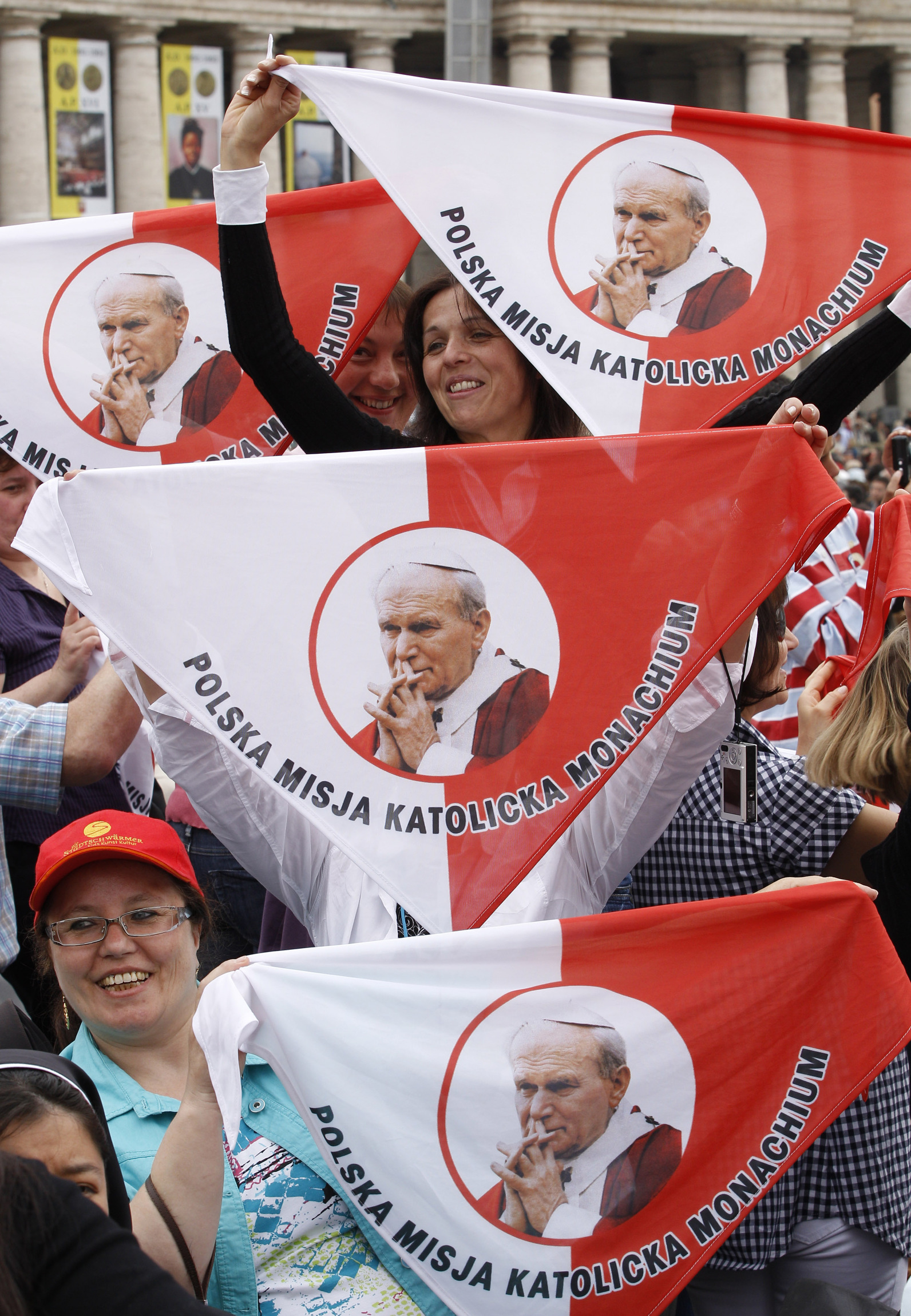 Pilgrims in St. Peter's Square hold up handkerchiefs featuring Blessed John Paul II the day after his beatification in 2011. The late Polish pontiff will be declared a saint, the Vatican said July 5, after officials approved a second miracle attributed to his intercession. (CNS photo/Paul Haring)