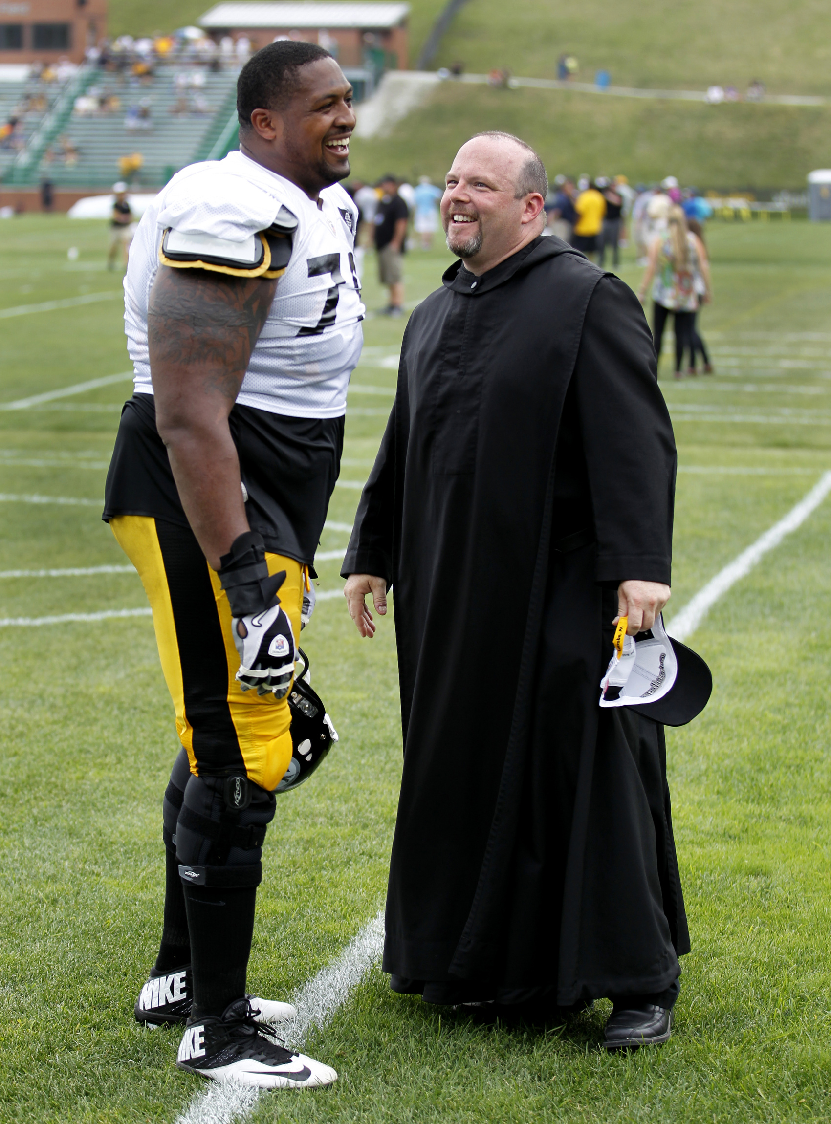 Benedictine Father Paul R. Taylor, executive vice president of St. Vincent College, and Pittsburgh Steelers' offensive guard Ramon Foster, share a laugh after a workout session at the Steelers' football training camp on the college campus in Latrobe, Pa.