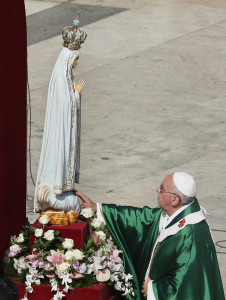 Pope Francis touches the original statue of Our Lady of Fatima after entrusting the world to Mary at the end of a Mass in her honor in St. Peter's Square at the Vatican Oct. 13.