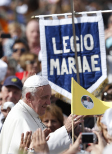 Pope Francis passes a Legion of Mary sign in Italian as he greets the crowd after celebrating Mass in honor of Mary in St. Peter's Square at the Vatican Oct. 13. The pope entrusted the world to Mary at the end of the Mass.