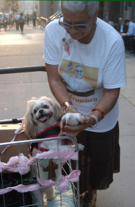 Lydia Matos of St. Paul-St. Agnes parish, Cobble Hill, presents her pets, Suzie, a Shih Tzu, and Lily, a dove. Matos placed Lily on Suzie's shoulders for part of the ceremony. (Photo by Marie Elena Giossi)