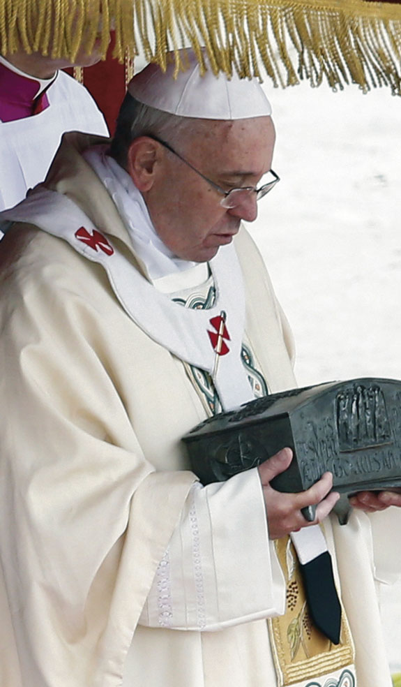 Pope Francis holds a bronze reliquary containing the relics of St. Peter the Apostle on the altar during a Mass in St. Peter's Square at the Vatican. The bone fragments were discovered during excavations of the necropolis under St. Peter's Basilica in the 1940s. Photo © Catholic News Service