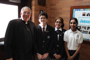 Bishop Nicholas DiMarzio was all smiles during his Catholic Schools Week visit to Immaculate Conception School, Jamaica Estates. He's pictured with, from right, eighth grader Anjali Deodat, seventh grader Ariel Narine and eighth grader Carlos Carranza. (Photo by Jim Mancari)