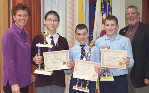 Dorothea Breen, principal of Immaculate Conception School, and Anthony Biscione, deputy superintendent, congratulate math bee winners, Nicholas Vidal, Frank D'Elia, and John Lavelle.
