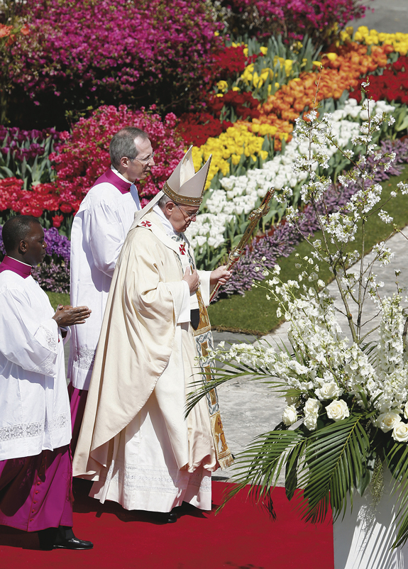Pope Francis walks past flowers as he leaves after celebrating Easter Mass in St. Peter's Square.