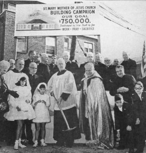"A photo printed in The Tablet in October, 1968, shows Father Francis X. Reilly (left), pastor, and Msgr. Joseph Wiest, then-SW Kings dean, wielding shovels at the groundbreaking of the church. Above the crowd is a building campaign sign declaring a $750,000 goal with the theme: ""Destroyed by Fire...Built by Love.""."