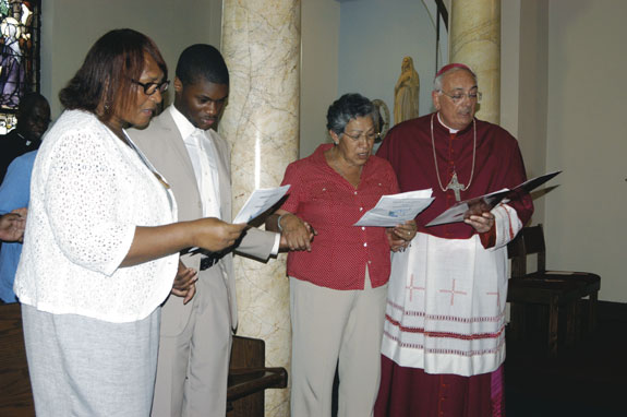 "Bishop Nicholas DiMarzio, far right, joined other people of faith in singing ""We Shall Overcome"" during an ecumenical prayer service for peace and reconciliation at St. Peter Claver Church, Bedford-Stuyvesant, Sept. 6."