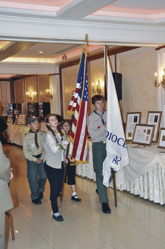 From left, Webelo Scout Gabe Gutierrez, Girl Scouts Emily and Lauren Caccamo and Boy Scout Anthony Caccamo, all from Holy Name, Park Slope, present the colors at the annual Bishop's Dinner for Scouting.