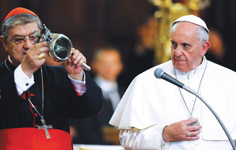 Pope Francis looks at a reliquary containing what is believed to be the liquefied blood of St. Januarius during a meeting with religious in Naples, Italy, March 21. Cardinal Crescenzio Sepe of Naples, holding the reliquary, announced that the dried blood of the saint had begun liquefying after the pope handled the reliquary. (Photo by Catholic News Service/Paul Haring)