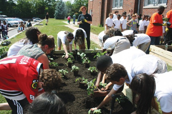 Students from St. Gregory the Great School, Bellerose, prepare the P.O. Brian Moore Memorial Garden that will be dedicated June 20. It honors the police officer who was murdered earlier this year while on duty in Queens Village.