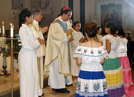 San Salvador Archbishop Jose Luis Escobar Alas receives the offertory from young ladies dressed in Salvadoran garb. He visited Presentation of the Blessed Virgin Mary parish, Jamaica, to celebrate a Mass in honor of Blessed Oscar Romero and to encourage the faithful to pray for his canonization.