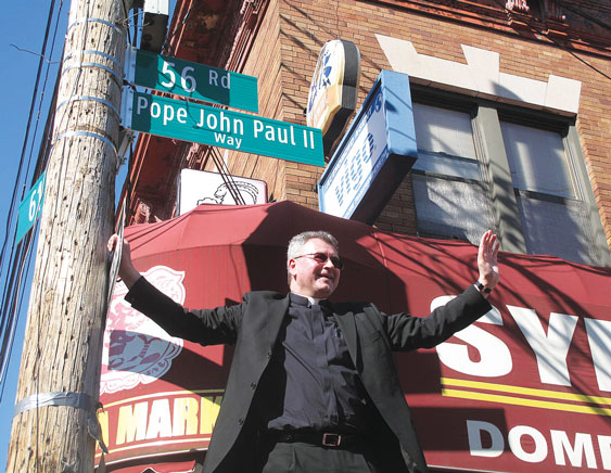 As pastor of Holy Cross parish, Maspeth, then-Father Mroziewski smiles after unveiling the official street sign declaring the block on which Holy Cross Church stands as Pope John Paul II Way.
