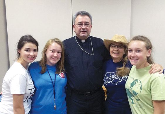 Bishop Mroziewski poses with young women involved in the Polish Scouting movement at Holy Cross parish and Our Lady of Czestochowa-St. Casimir.