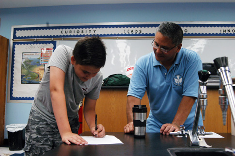 Cathedral Prep's Jeremy Reyes, science teacher, works with a student at the school's Troike Summer Leadership Program. This year the school launched a new program to give students extra academic support.