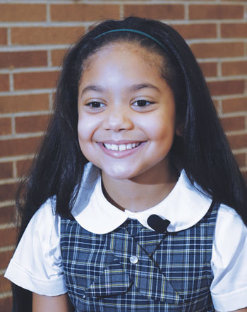 Allison Reyes, a third-grader at Our Lady of the Angels School in the East Harlem, smiles during an Aug. 20 news conference to outline details of Pope Francis' visit to the school in September. (Photo by Catholic News Service/ Chris Sheridan)