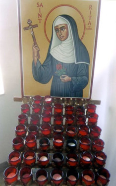 Artwork of St. Rita behind a candle rack at Our Lady of Redemption Church in Warren, Michigan. (Photo by Catholic News Service/Mark Pattison)