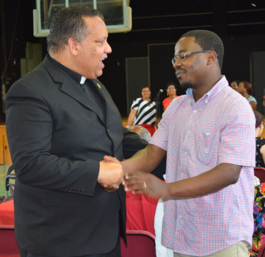 Father Maurice Nutt, C.Ss.R. speaks with an audience member after delivering his keynote address at the Brooklyn Diocese Vicariate of Black Catholic Concerns Praise Prayer Brunch at St. Thomas Aquinas, Flatlands. The People of Praise band plays in the background.