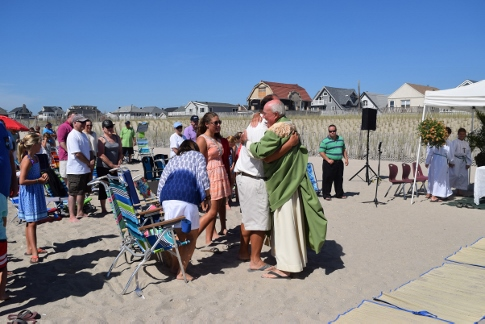 St. Francis de Sales parish celebrated the end of summer with a Sunday Mass on the beach.  Msgr. John Bracken, administrator, exchanges the sign of peace with participants.