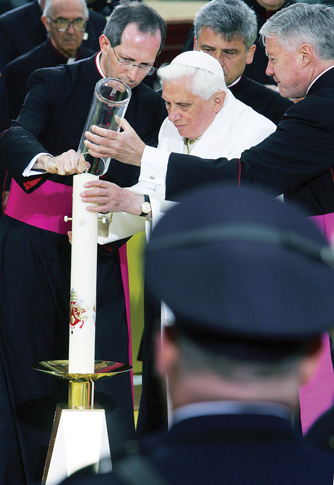 Clergymen assist Pope Benedict XVI as he lights a candle at ground zero in 2008 inside the cement-walled crater where New York's World Trade Center towers once stood. Pope Francis will visit ground zero during his Sept. 22-27 visit to the United States. (Photo © Catholic News Service/Alessia Giuliani, Catholic Press Photo)