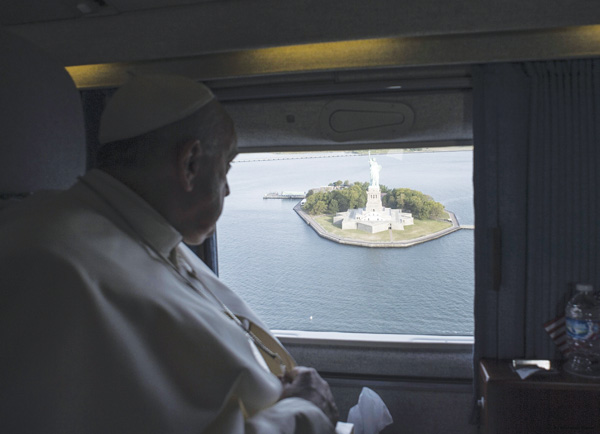 Pope Francis looks out at the Statue of Liberty while flying over New York Harbor on his way from New York to Philadelphia Sept. 26. (Photo © Catholic News Service/L'Osservatore Romano via Reuters)