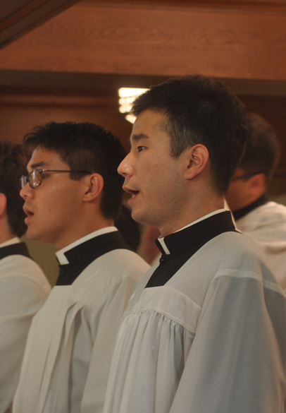 Two seminarians sing in the schola during the liturgy.