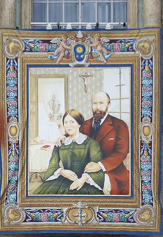 p A tapestry of Louis and Zelie Martin, parents of St. Therese of Lisieux, hangs from a balcony as Pope Francis leads the Oct. 18 Mass for their canonization.