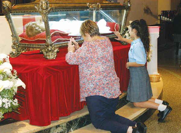 Maria Resciniti, sixth-grade teacher at Good Shepherd Catholic Academy and one of her students kneel before the relics of St. Maria Goretti at Good Shepherd Church in Marine Park. (Photo © Marie Elena Giossi)
