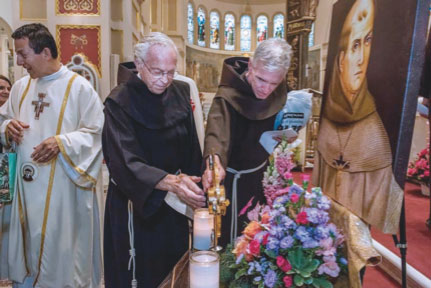 Franciscan friars touch the cross-shaped reliquary holding relics of St. Junipero Serra at the Franciscan Monastery of the Holy Land in Washington Sept. 24. (CNS photo/Karen Kasmauski)