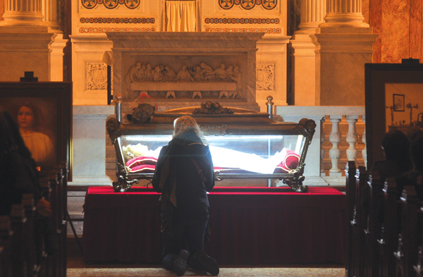 A woman kneels before the relics of St. Maria Goretti at St. Joseph Co-Cathedral, Prospect Heights, where they were displayed for veneration Oct. 2. (Photo © Ed Wilkinson)