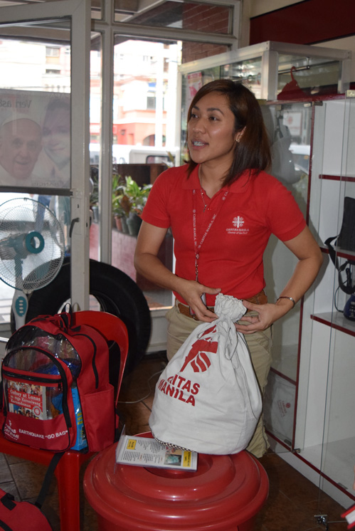 Gilda Avedillo, program officer at Caritas Manila, shows emergency response backpack and family bucket with food in case of emergencies. (Photos © Maria-Pia Negro Chin)