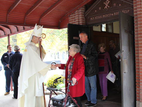 Auxiliary Bishop Paul Sanchez greets the faithful at Holy Cross Cemetery, Flatbush, after celebrating an All Souls Day Mass, Nov. 2.