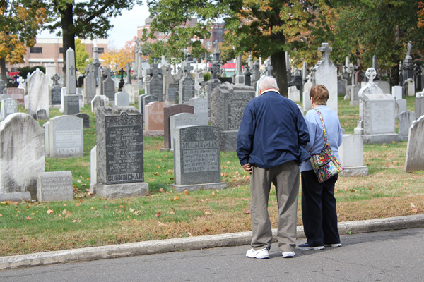 Basil and Susan Burgess read the names on gravestones near the chapel at Holy Cross Cemetery, Flatbush, on All Souls Day, Nov. 2. (Photos © Marie Elena Giossi)
