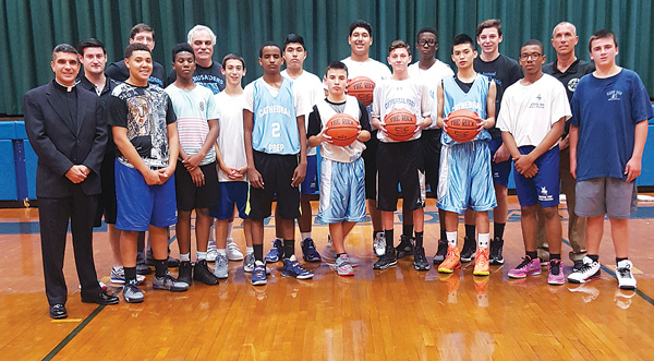 p The Cathedral Prep and Seminary community welcomed over CYO basketball coaches to the school for the annual coaches clinic. Cathedral rector, Father Joe Fonti is at the left and CYO director, Rob Caldera is second from right.