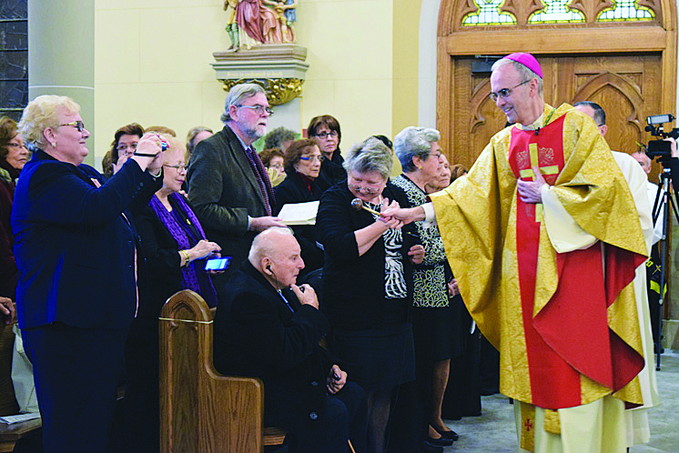 Auxiliary Bishop Paul Sanchez, former pastor, sprinkles holy water on the congregation at the beginning of a dedication Mass Nov. 14. The Mass kicked off the parish's 175th anniversary year.
