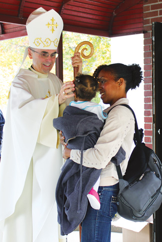 Auxiliary Bishop Paul Sanchez blesses Cyndie Lai-Fang and her daughter, members of St. Rose of Lima parish, Parkville, after an All Souls Day Mass at Holy Cross Cemetery, Flatbush, Nov. 2. Field Masses were celebrated at several diocesan cemeteries.