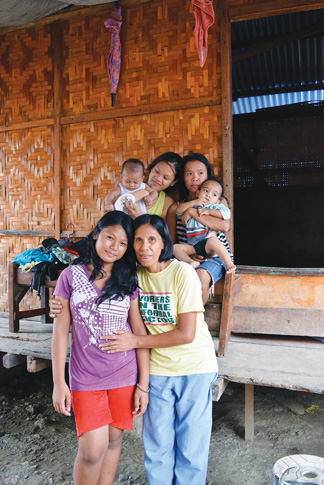 Emelinda Condeza poses with her daughters and grandchildren in front of her new temporary shelter.