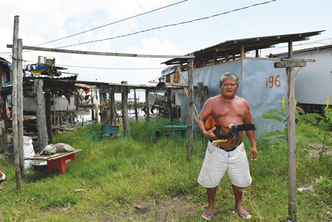 In Old Road Sagkahan, Tacloban, a man poses around settlements that were rebuild after Super Typhoon Haiyan. Because the houses are at risk of flooding, around 200 families living there will need to relocate.