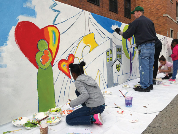 Hour Teen Scene members, joined by artist Derrick Little, create a beautiful mural reflecting their life experiences outside their Ravenswood residence. (Photos courtesy of Hour Children)
