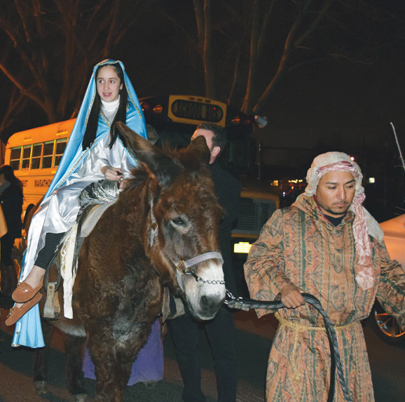Eighth-grader Sophia Deveikis, portrayed Mary as she rode a donkey to the wooden manger in front of the school.