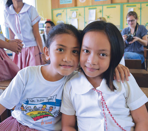 Students at an elementary school in nearby Tolosa ­– Katrina Nuevas and Neamae Varona – hug each other during a school visit. Their community was greatly affected by the typhoon.