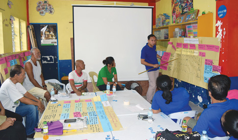 Community leaders and members of Barangay Luntad in Palo, Leyte, write down the town's emergency plans in case of disasters at an Oct. 29 meeting. Town members were among the millions of Filipinos affected by Super Typhoon Haiyan which devastated the country after landing on Nov. 8, 2013.
