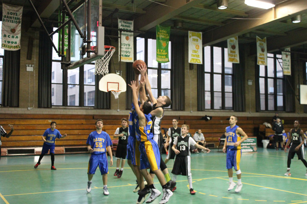 p Eighth graders from St. Athanasius and St. Columba parishes battle for the basketball during the annual Giving Thanks Basketball Classic at St. Thomas Aquinas' Msgr. King Gym in Flatlands. (Photo by Jim Mancari)